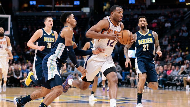 Jan 19, 2018; Denver, CO, USA; Phoenix Suns forward T.J. Warren (12) makes a move to the basket as Denver Nuggets guard Gary Harris (14) defends during the in the first quarter at the Pepsi Center. Mandatory Credit: Isaiah J. Downing-USA TODAY Sports