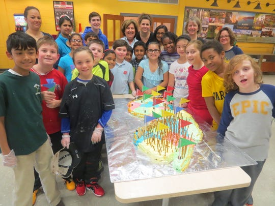 Fourth-grade students at The Wardlaw-Hartridge School in Edison display the New Jersey state cake they created in the AP Room. The young bakers are joined by their teacher, Ellen Ritz of Piscataway, several parent volunteers and senior buddies