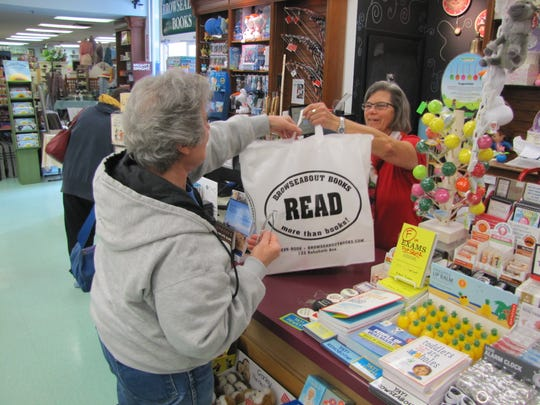 Bookseller Helen Barger gives a bag of goods to customer Rose Fiechter of Dagsboro at Browseabout Books in Rehoboth Beach. The bookstore celebrates its 40th anniversary this year.