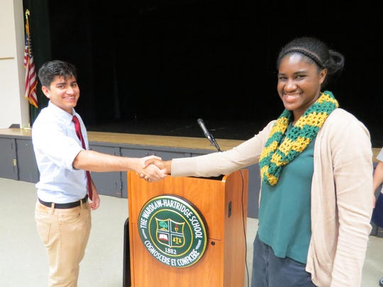 Camille Menns of New Brunswick, a senior and Student Council president at The Wardlaw-Hartridge School in Edison, shakes hands with junior Astitva Soni of Edison at her final morning meeting on May 18. Menns handed over control of W-H podium to Soni, who was elected the new Student CouncilpPresident. Menns thanked her fellow officers, friends and teachers for their support during her tenure.