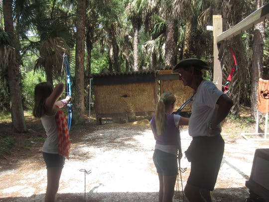 Ben Brown, the vice president of Lee County Archers, helps home schoolers on a recent Thursday during Open Shooting.