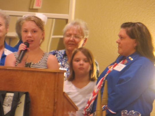 Ladies Auxiliary Junior Girls Madison Constance (left, at lectern) and Janna Roberson receive awards at the VFW annual state convention June 25-28 in Alexandria.