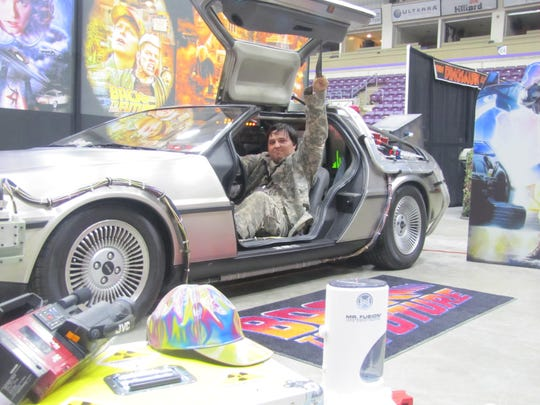 "Randy Gray Jr., of Plymouth, Pa., gets his photo taken in a 1982 DeLorean, outfitted like the car in the ""Back to the Future"" movies, on Saturday at Twin Tiers Comic-Con at First Arena, Elmira."