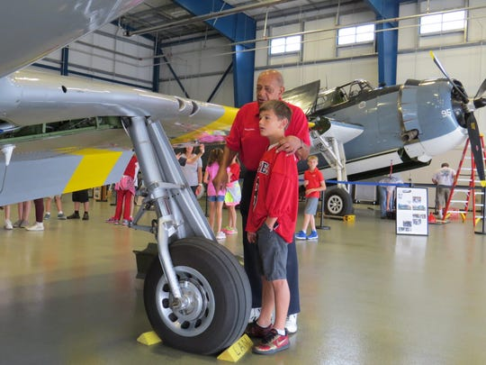"Tuskegee Airman Retired Lt. Colonel Dr. Harold Brown shows Cameron Gillum features of the Red Tail airplane on exhibit during a field trip to the Liberty Aviation Museum and documentary ""Rise Above."""