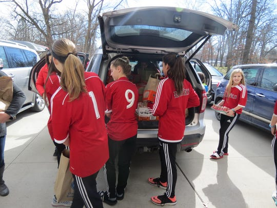 Soccer players unload donated items.