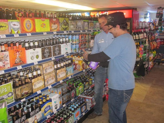Mike Palencar, left, and Tony Cashier show some of the beer products at the store.