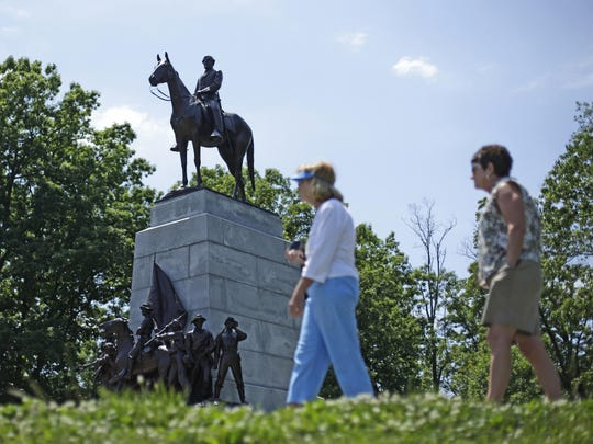 FILE -- In this June 5, 2013, file photo, a monument to Gen. Robert E. Lee mounted on his horse Traveller sits atop a ridge held by Confederate troops, above the field of Pickett's Charge in the Gettysburg National Military Park.