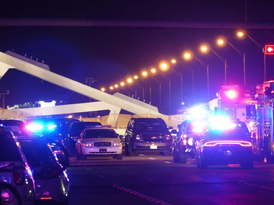 Police lights illuminate the scene of a pedestrian bridge collapse in Miami, Florida on March 15, 2018, crushing a number of cars below and reportedly leaving several people dead.