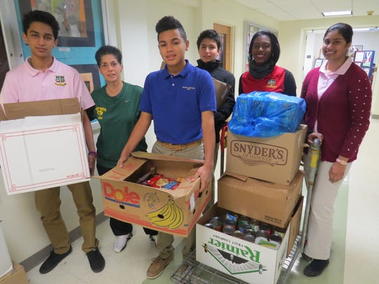 Freshmen Raj Raval of South Plainfield, Ovidio Chavez of Elizabeth, Eduardo Martinez of Scotch Plains, Brittney Wilson of North Plainfield and Sana Mansuri of Edison help Dawn Francavilla, director of student life at The Wardlaw-Hartridge School in Edison, load a cart with boxes for delivery to Hands of Hope and Starfish, the two charities for which the Upper School collected items during the recent holiday food drive.