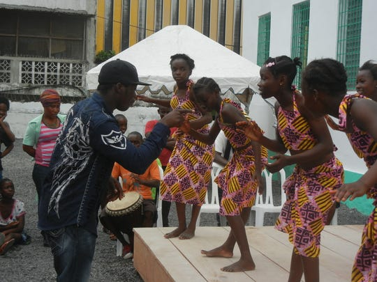 Souleymane Solo Sana, left, directs a group of girls as they prepare to perform at their school's opening ceremony in September 2014 in Monrovia, the Liberian capital. Sana is a professional dancer with an expertise in African dance traditions.