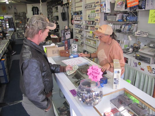 """Longtime customer Paul E. """"Eddy"""" Brusso Jr. of Elmira, purchases a pair of lighters Wednesday from Granny's Attic co-owner Leigh Roberts."""