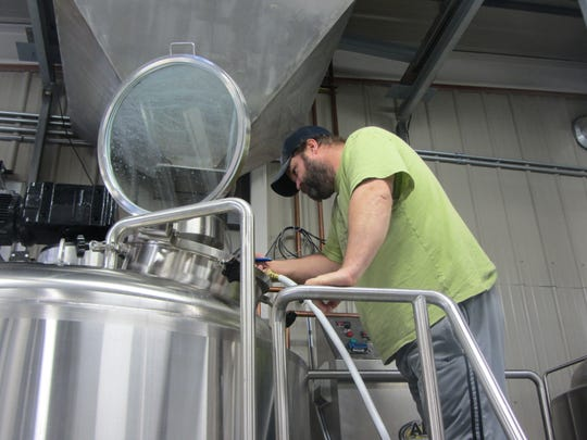 The head brewer for Black Eagle Brewery, Jason Lehman, washes out the mash tun in the 15-barrel capacity beer brewery that opened last week. Black Eagle Brewery, 1602 25th Ave. N.E. has a tap room and is capable of producing 2,000 barrels of beer a year.