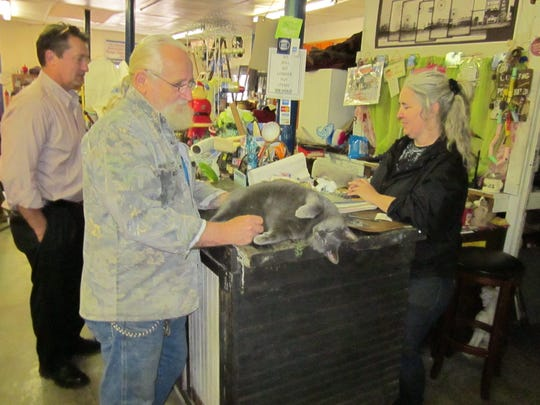Customer Larry Hawk talks to Denise Jenkins as he pets the shop cat, Mojo, who likes to jump onto the counter. Another customer, Stuart Rotramel, left, looks on.
