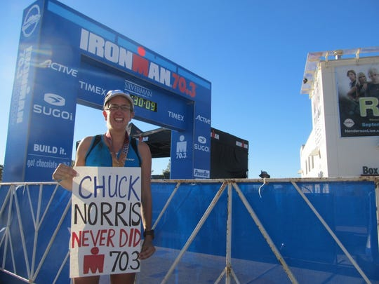Reporter Beth Roessner stands at the finish line of Ironman 70.3 Silverman holding one of her signs.