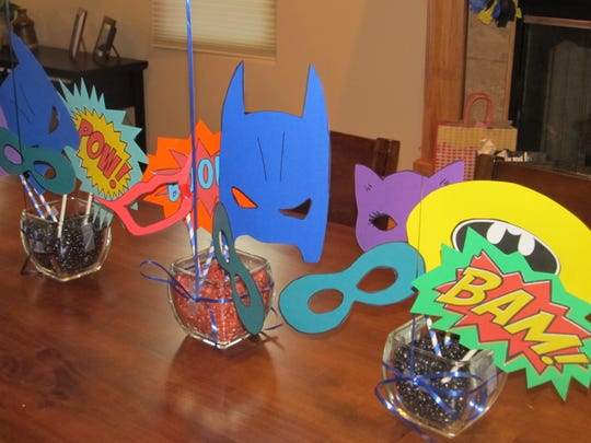 "Suzie Long cut out Batman, Robin, and Cat Woman masks using free patterns she found online as well as a few Batman-inspired words including ""Bam!"" and ""Zap!"" Then she taped each to patterned paper straws."