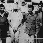 In this Nov. 9, 1979, file photo, one of the hostages seized when Islamic radicals stormed the U.S. Embassy in Tehran, blindfolded and with his hands bound, is displayed to the crowd outside the U.S. Embassy in Tehran by the Iranian hostage takers.