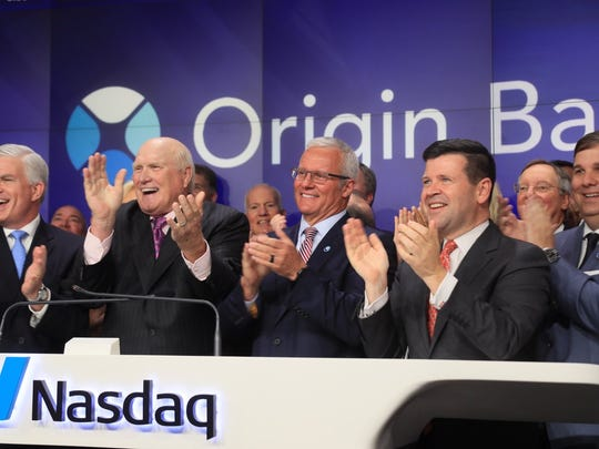 Front row, left to right: Steve Brolly, Origin Bank chief financial officer; Terry Bradshaw; Drake Mills, Origin's CEO; Bob McCooey, Nasdaq senior vice president; and Lance Hall, Origin's chief operating officer.