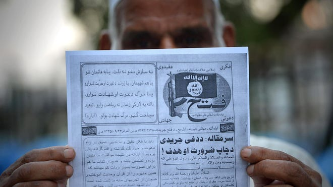 A man holds a pamphlet allegedly distributed by the Islamic State on Sept. 3, 2014, in Peshawar, Pakistan.