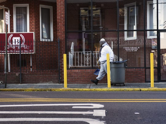 Former Paterson Councilman Anthony Davis sweeping up at Bragg Funeral Home. He works two part-time jobs.