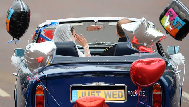 Britain's Prince William drives an Aston Martin as he leaves the Buckingham Palace with his wife Kate, Duchess of Cambridge, after their wedding service on April 29, 2011, in London.