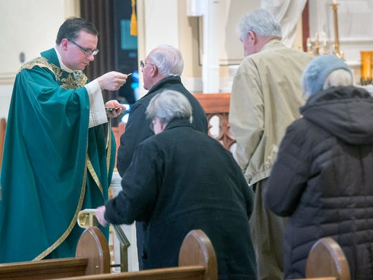 Father Jonathan Sawicki offers communion during an 8 a.m. morning mass at the Immaculate Conception Church in York.