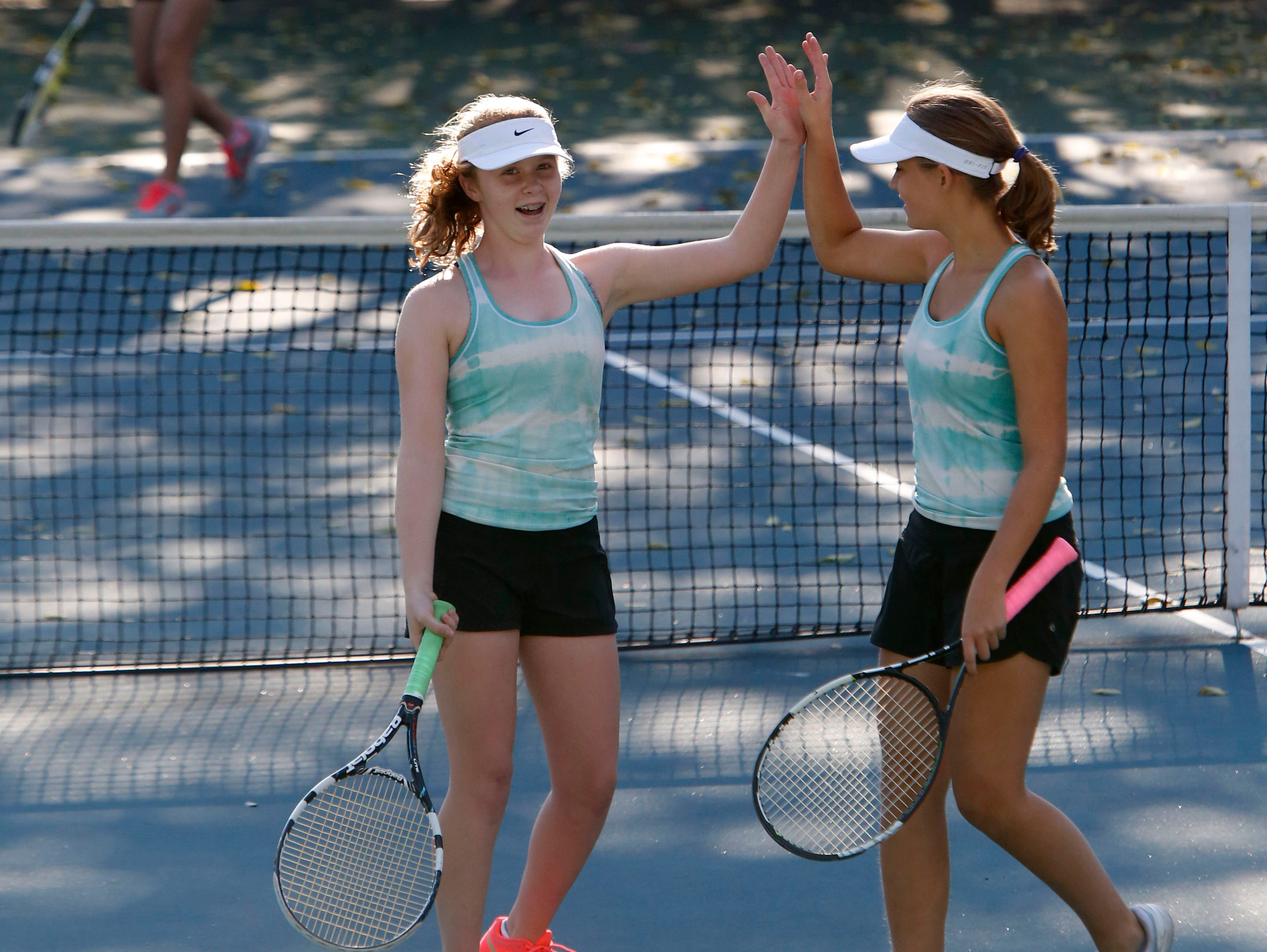 Bronxville's Katharine Frost, left, and teammate Eva Dani hi-five during a doubles game against Rye Neck's Mizuki Shionoya and Clemence Balzano in the Conference III tennis tournament Oct. 15, 2015 at Edgemont High School in Scarsdale.