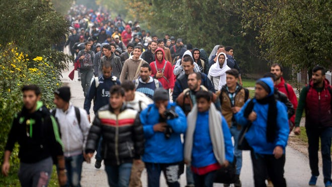 Migrants and refugees walked Oct. 16, 2015, toward Austria at the former border station of Hegyeshalom, at the Austrian border west of Budapest, Hungary. International Organization for Migration said that more than 600,000 people had arrived by sea into Europe this year and more than 3,000 of them died trying to reach Europe to escape war or poverty.