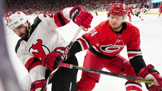 New Jersey Devils forward Kyle Palmieri (21) and Carolina Hurricanes defensemen Jaccob Slavin (74) goes after the puck up against the glass during the first period at PNC Arena on Friday, March 2, 2018.