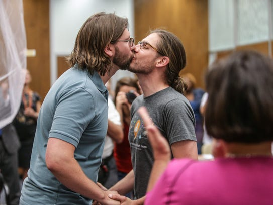 Craig Bowen, left, and  Jake Miller kiss after being married by Marion County Clerk Beth White, center, in Indianapolis, Wednesday, June 25, 2014.  A federal judge struck down Indiana's ban on same-sex marriage Wednesday in a ruling that immediately allowed gay couples to wed. (AP Photo/The Indianapolis Star, Michelle Pemberton )  NO SALES