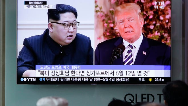 People at a Seoul railway station watch a TV screen showing President Trump and North Korean leader Kim Jong Un.