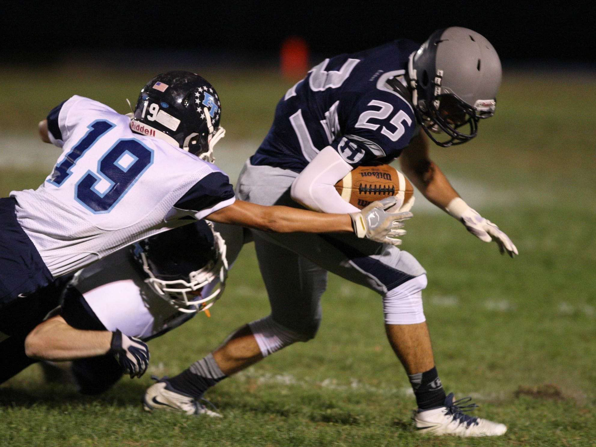 Nick Chianca, #25 Howell, tries to break free of Pat Laricy, #19 Freehold Township, in a football game Friday, September 25, 2015, at Howell High School.