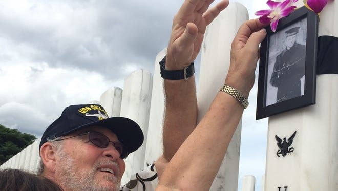 Edwin Hopkins of Runnemede and sister Faye Hopkins Boore place orchids at the USS Oklahoma Memorial on Ford Island in Pearl Harbor, Hawaii. Their uncle, also named Edwin Hopkins, was a crew member killed in the 1941 harbor attack who was only recently identified.