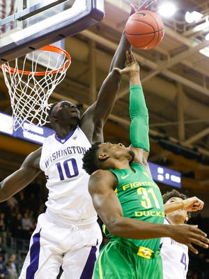 Huskies forward Malik Dime (left), shown blocking a shot against Oregon last week, is expected to miss 4-5 weeks with a broken right pinky.