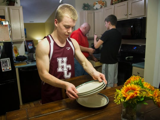 Adrian Kjellen, 17, of Nykšping, Sweden, from left, helps set the table for dinner with Monte Troutman and Ty Troutman, 16, at their home in Henderson, Wednesday, March 8, 2017. Kjellen is an exchange student currently living with the Troutman family in Henderson.