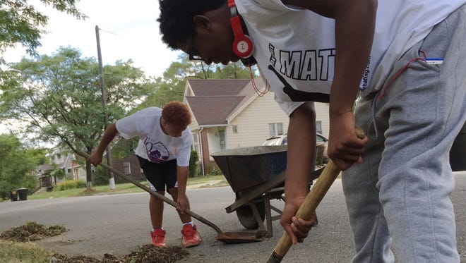 On a side street near Harper and Chalmers on Detroit's east side, Taran Sherman, 14, uses a pick-axe to loosen weeds from the curb while his friend Zaire Thomas, 13, shovels up debris Saturday, Aug. 6, 2016.