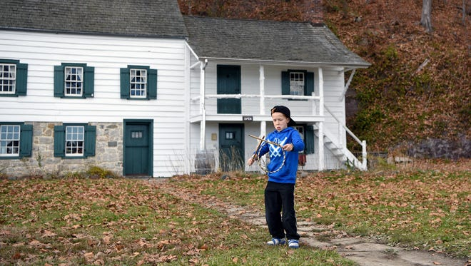 Colin Hill 9 of Montvale, catches a wooden hoop while playing the 19th century game of graces outside The Kearney House located within the Palisades Interstate Park in Alpine on Sunday, November 27, 2016. The house is listed on both the National and New Jersey State Historic Registers.