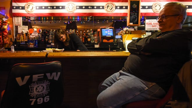 James Hindes sits at the bar in the VFW Post 796 in Port Huron, while auxiliary member Susan Williams tends the bar Dec. 13. Last week, the Michigan Liquor Control Commission announced support of a bill that would amend the state's Liquor Control Code to allow members to purchase their own beer at posts besides their own.