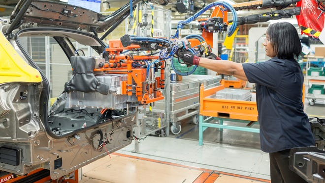In this photo provided by the BMW plant in Spartanburg, a production worker installs the plant's 25,000th electric battery on May 15,2017.