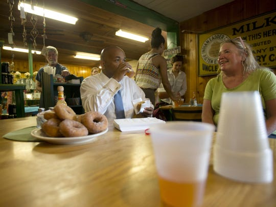 Assembly Speaker Carl Heastie, D-Bronx, samples cider and donuts while talking with Laura Ten Eyck at Indian Ladder Farms in Altamont