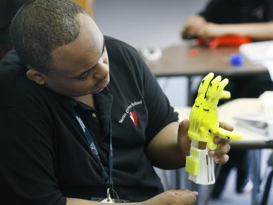 Vertus Charter School 10th-grader Justin Hampton tests the wires on a prosthetic hand made with a 3-D printer.