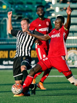 Rochester Rhinos' Christian Volesky and Richmond Kickers' William Yomby battle for the ball in the first half at the Rochester Rhinos Stadium.