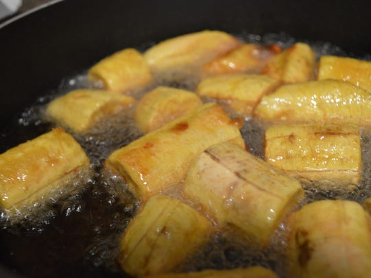 Plantains are fried until lightly golden before being crushed in a mortar to create mofongo.