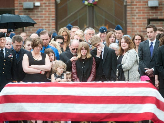 Family, friends and members of the military gather outside of St. Lawrence Church in Essex Junction after Kryn Miner's funeral on Friday. Miner was a 44-year-old combat veteran who served with the Vermont Army National Guard.
