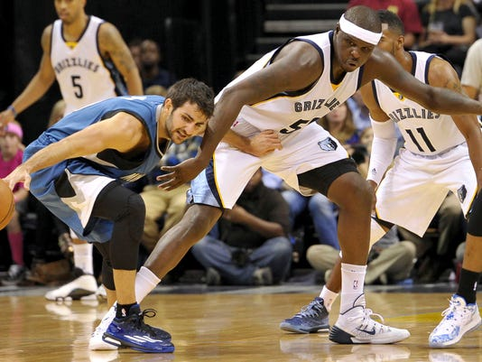 Minnesota Timberwolves guard Ricky Rubio, left, struggles for control of the ball against Memphis Grizzlies forward Zach Randolph in the first half of an NBA basketball game Wednesday, Oct. 29, 2014, in Memphis, Tenn. (AP Photo/Brandon Dill)