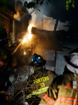 Firefighters knock down part of a structure roof that caught fire from a broken gas line Thursday, Nov. 5, 2015, in Jefferson. Jefferson Borough Fire Department assistant chief Mark Becker said the gas meter in a utility structure behind Roger Miller's home, which dates back to at least the 1830s, was broken and spewing gas that provided constant fuel for the flames.
