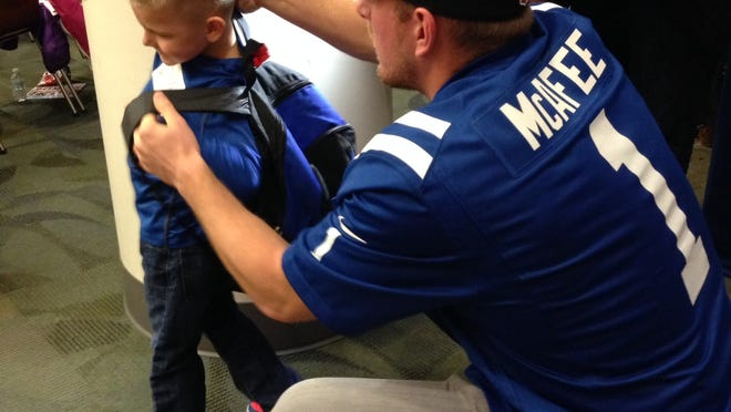 Colts punter Pat McAfee gives Kaleb Tucker a hand with his backpack during the Books for Youth event.