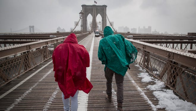 epa04586538 Tourists walk over the Brooklyn Bridge ahead of a large winter storm in New York, New York, USA, 26 January 2015. Areas of the New York metropolitan region were expected to get up to two feet of snow.  EPA/ANDREW KELLY 0 ORG XMIT: AK014