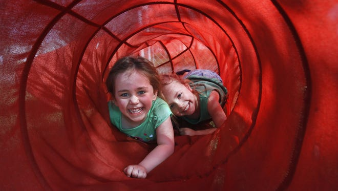 Carlee Jones and Izzabella Thornboro play in the tunnel on the playground at the United Day Care Center in this file photo from 2012.