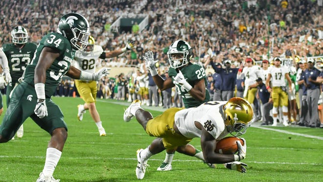 Sep 23, 2017; East Lansing, MI, USA; Notre Dame Fighting Irish running back Dexter Williams (2) dives into the end zone for a touchdown as Michigan State Spartans linebacker Antjuan Simmons (34) and cornerback Josiah Scott (22) defend in the second quarter at Spartan Stadium. Mandatory Credit: Matt Cashore-USA TODAY Sports