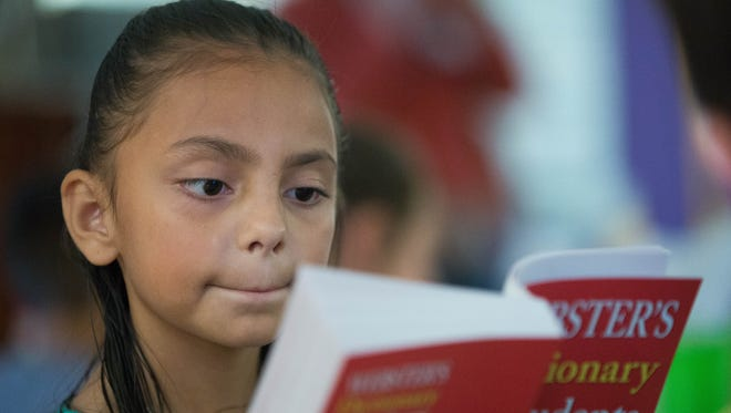 Jaylene Rogers, 8, a third-grader at Sunrise Elementary School, looks through a dictionary given to her by the Rio Grande Rotary Club. The club donated dictionaries to every third-grader in Las Cruces on Tuesday, March 28, 2017. The Rio Grande Rotary Club has given out more than 20,000 dictionaries to third-graders in the past decade.